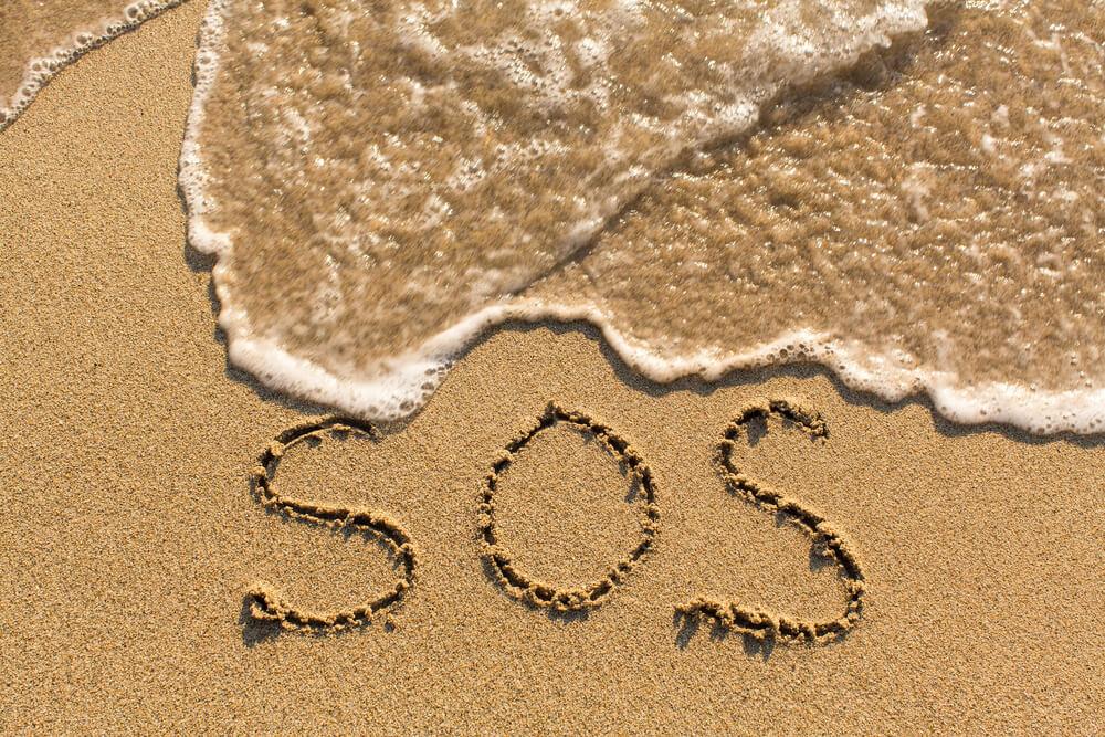 砂浜に書かれたSOSのメッセージ