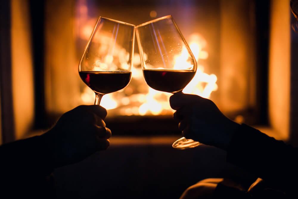 暖炉の前でワインで乾杯をする様子