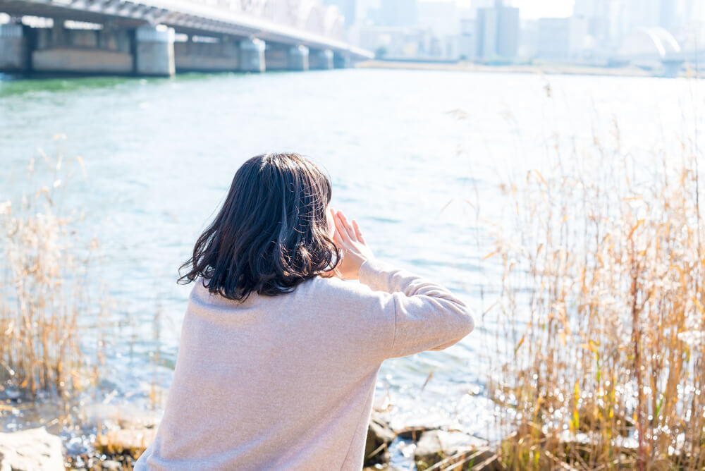 大きい川に向かって叫ぶ女性