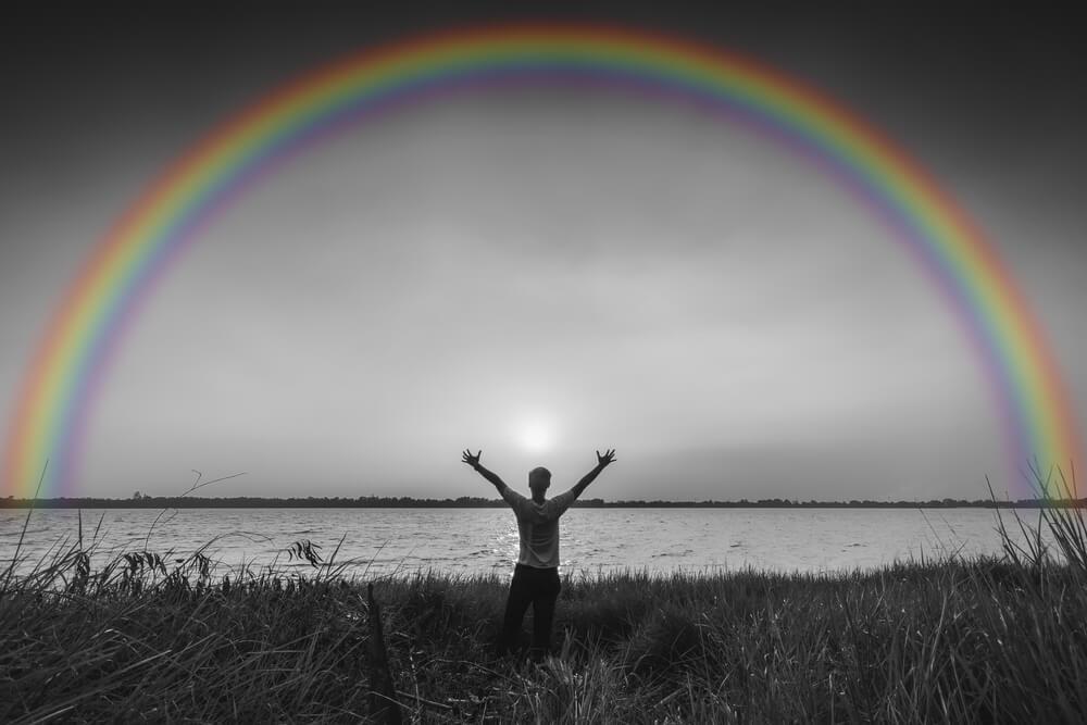 虹と空に向かって両手を突き上げている男性