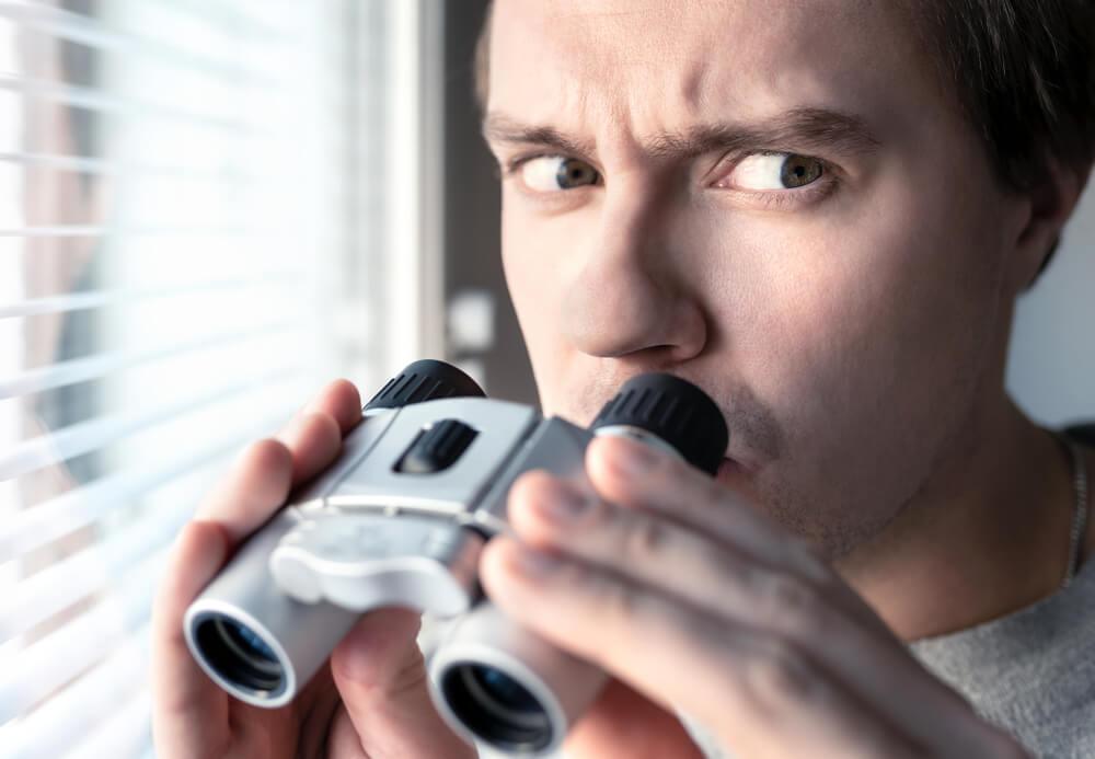 疑い深そうに望遠鏡を覗く男性