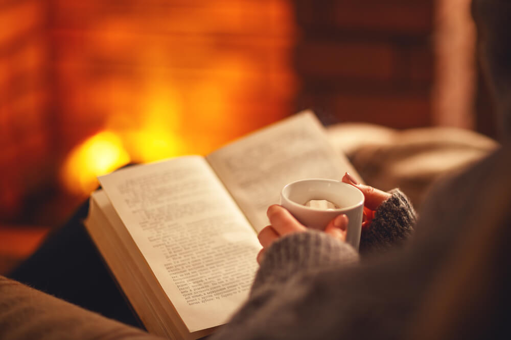 暖炉の前でマグカップを手に本を読む様子