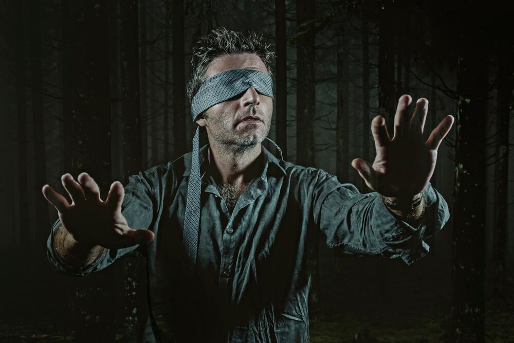 暗闇の中で目隠しをされ手探りしている男性