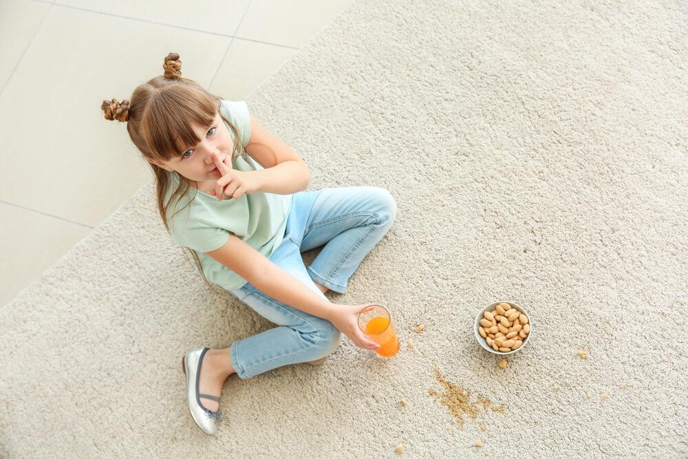 ジュースやお菓子をこぼしている少女