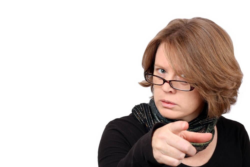 怒った表情でこちらを指差す女性