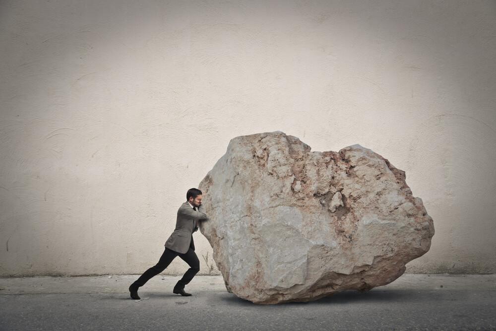 岩を動かすことに死力を注ぐ男性