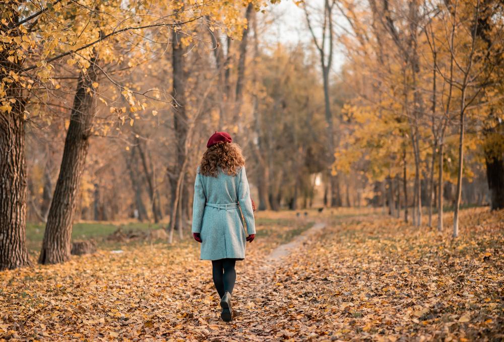 秋の美しい景色の中、逍遥する女性