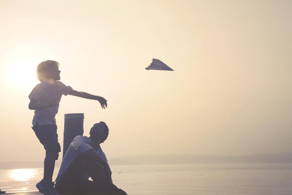 咄嗟に紙飛行機を投げる少年